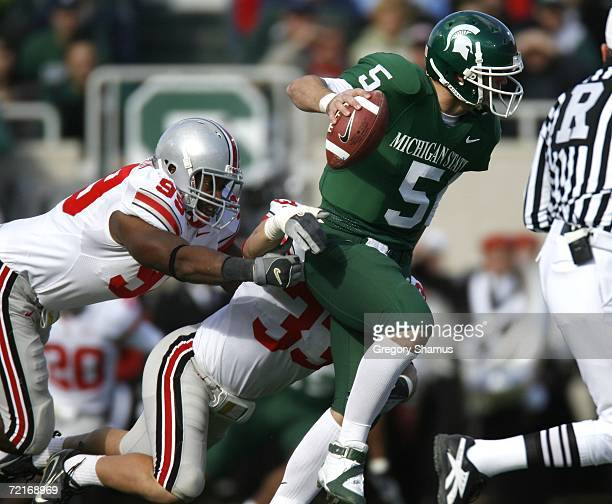 Drew Stanton of the Michigan State Spartans tries to escape the tackle of Jay Richardson and James Laurinaitis of the Ohio State Buckeys during first...