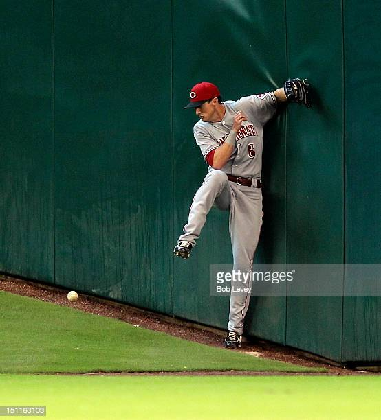 Drew Stubbs of the Cincinnati Reds runs into the wall as he attempts to make a catch off the bat of Fernando Martinez of the Houston Astros at Minute...