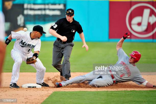 Drew Stubbs of the Cincinnati Reds slides into second base as Omar Infante of the Florida Marlins misses the ball during game one of a MLB...