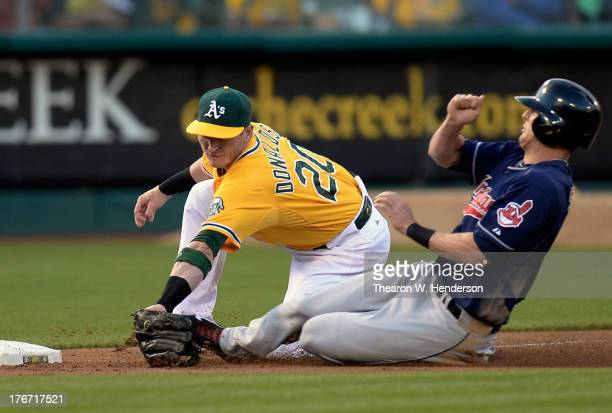 Drew Stubbs of the Cleveland Indians is thrown out at third base tagged by Josh Donaldson of the Oakland Athletics in the fifth inning at Oco...