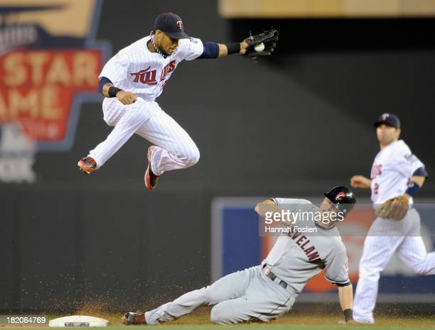 Drew Stubbs of the Cleveland Indians steals second base as Pedro Florimon of the Minnesota Twins fields the ball during the eighth inning of the game...