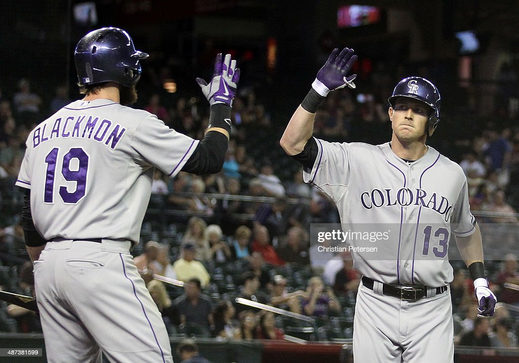 Drew Stubbs #13 of the Colorado Rockies high-fives Charlie Blackmon #19 after Stubbs hit a solo home run against the Arizona Diamondbacks during the ninth inning of the MLB game at Chase Field on April 29, 2014 in Phoenix, Arizona. The Rockies defeated the Diamondbacks 5-4.
