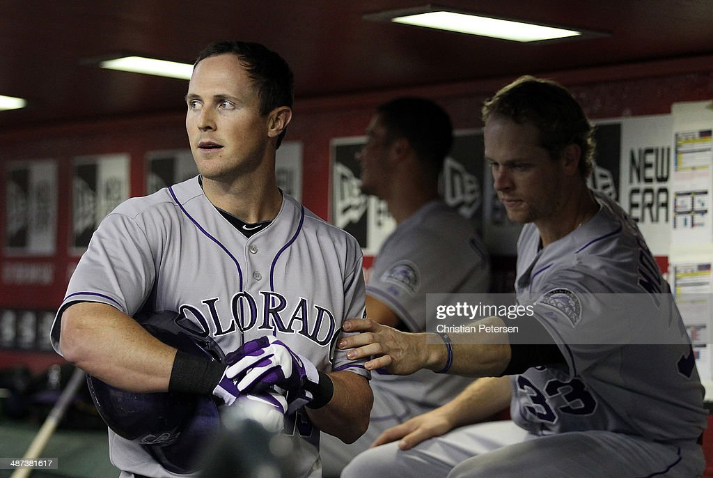 Drew Stubbs #13 of the Colorado Rockies is congratulated in the dugout by Justin Morneau #33 after Stubbs hit a solo home run against the Arizona Diamondbacks during the ninth inning of the MLB game at Chase Field on April 29, 2014 in Phoenix, Arizona. The Rockies defeated the Diamondbacks 5-4.