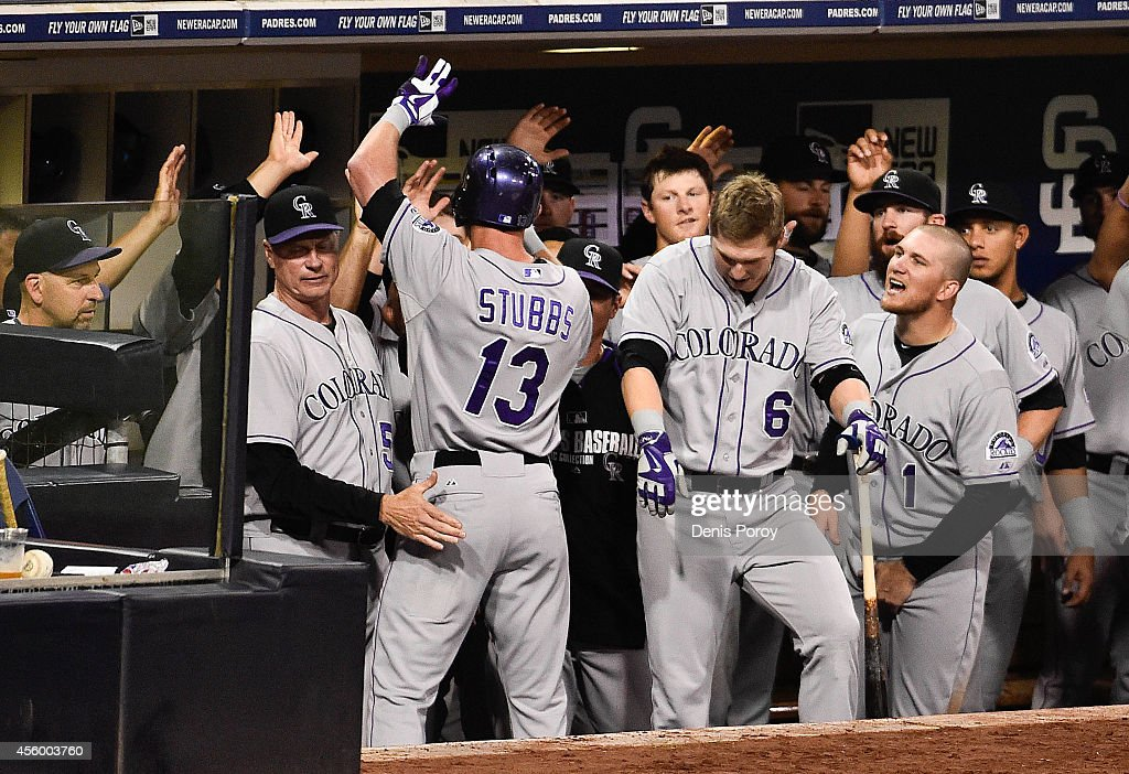 Drew Stubbs #13 of the Colorado Rockies is congratulated in the dugout after he hit a solo home run during the eighth inning of a baseball game against the San Diego Padres at Petco Park September, 23, 2014 in San Diego, California.