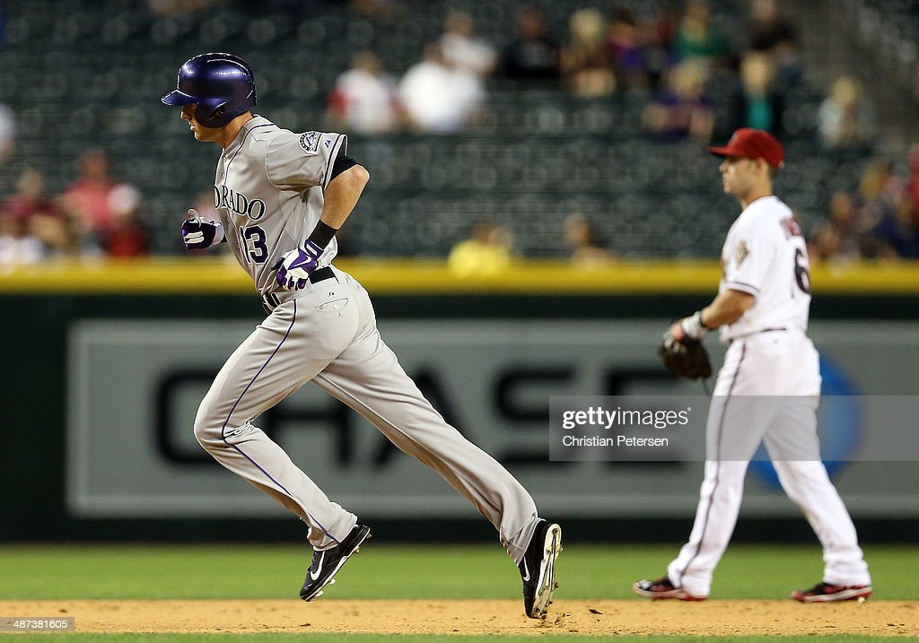 Drew Stubbs #13 of the Colorado Rockies rounds the bases past infielder Chris Owings #16 of the Arizona Diamondbacks after Stubbs hit a solo home run during the ninth inning of the MLB game at Chase Field on April 29, 2014 in Phoenix, Arizona. The Rockies defeated the Diamondbacks 5-4.