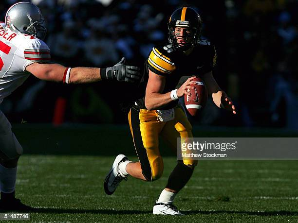 Drew Tate of Iowa looks for an open receiver while being chased out of the pocket by Simon Fraser of Ohio State October 16 2004 at Kinnick Stadium in...