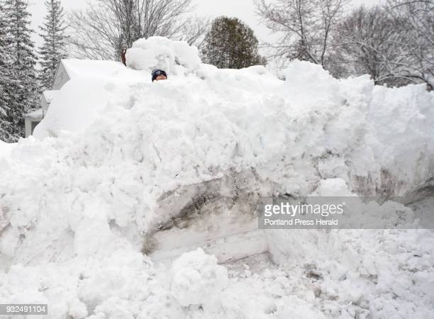 Drew Vessels peaks above a large pile of plowed snow while having a snowball fight with his father Dan before heading to school in Sanford on...
