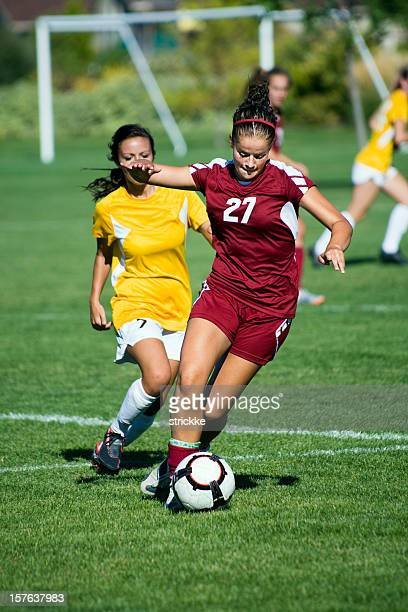 dribbling female soccer player breaks away from defense - face off sports play stock photos and pictures