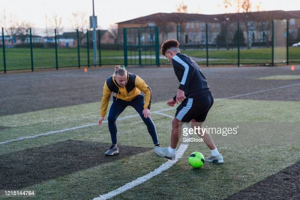 dribbling the ball - defender soccer player stock pictures, royalty-free photos & images