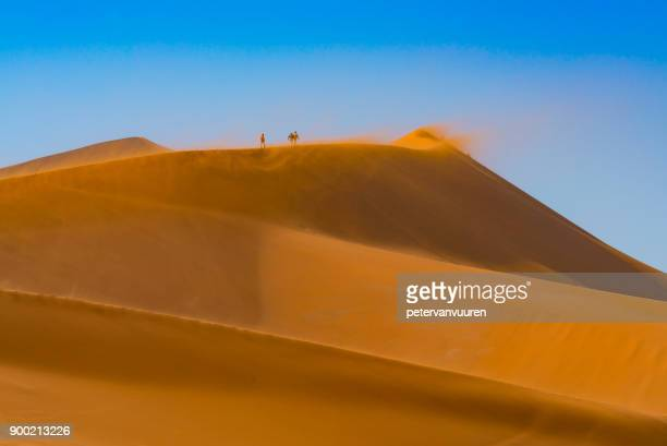 Drie mensen lopen op de stuivende zand duinen