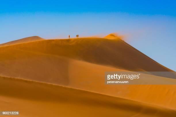 drie mensen lopen op de stuivende zand duinen - drie personen stock-fotos und bilder
