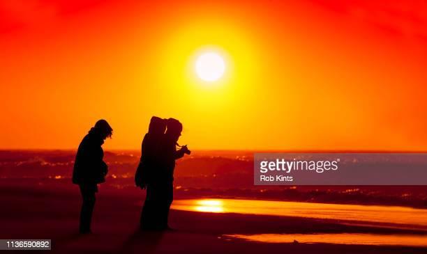 drie vrouwen proberen zich staande te houden en foto te maken in een storm op het strand - drie personen stock-fotos und bilder