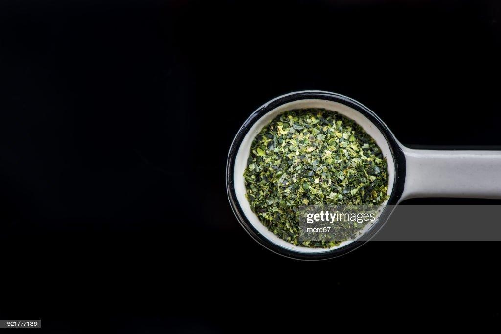 Dried aonori seaweed flakes on spoon : Stock Photo