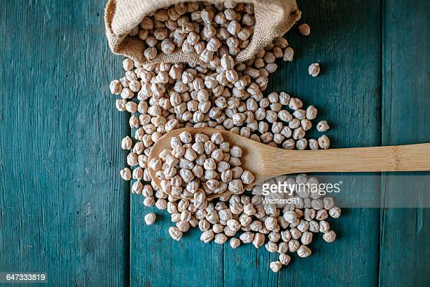 Dried chickpeas and wooden spoon on wood