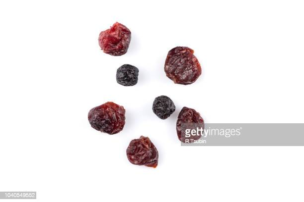 dried cranberries, cherries and blueberries on white background - dried food stock pictures, royalty-free photos & images