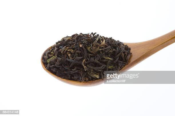 Dried darjeeling tea leaves in wooden spoon