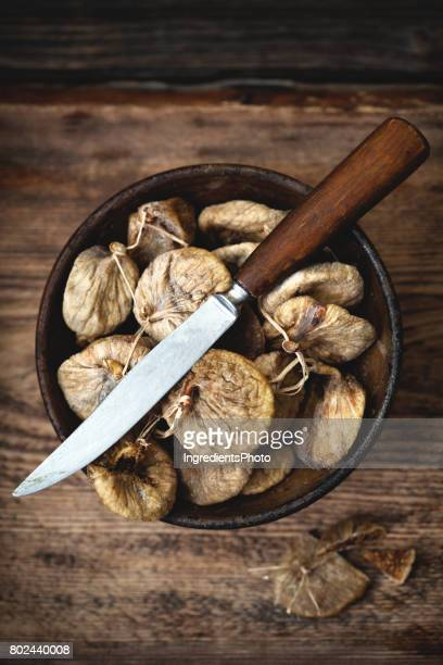 Dried figs in a brown bowl with a knife on wooden table.