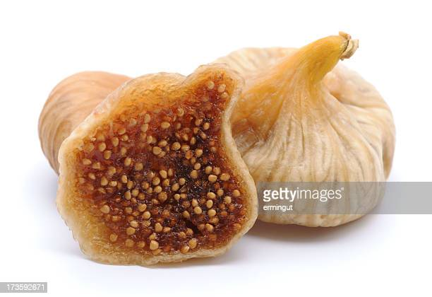 Dried figs with one chopped in half isolated on white
