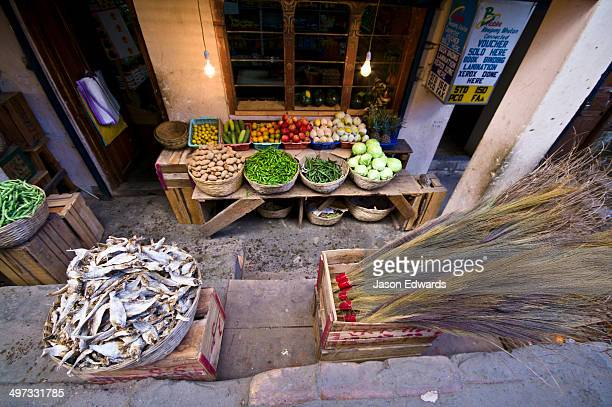 dried fish, grass brooms and vegetables for sale at a small general store. - 干物 ストックフォトと画像