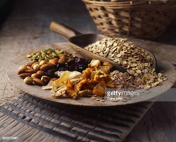 Dried fruits, nuts and oats on wooden plate