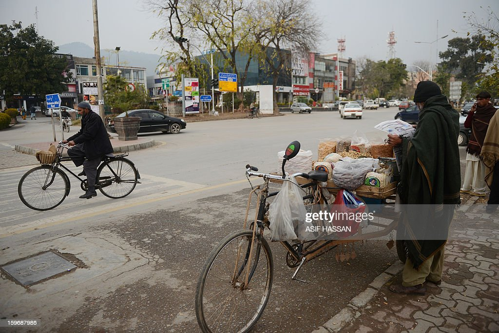 A dried fruits vendor (R) reads a newspaper while waiting for customers a day after a massive protest march in Islamabad on January 17, 2013