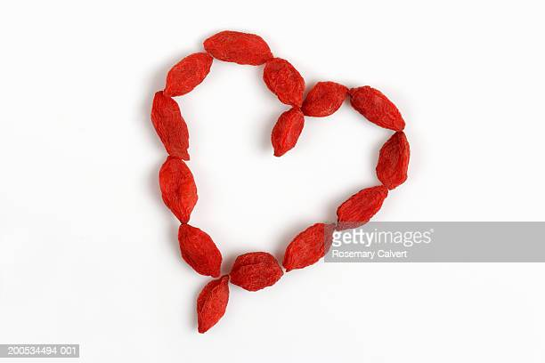Dried goji berries in heart shape, against white background, close-up