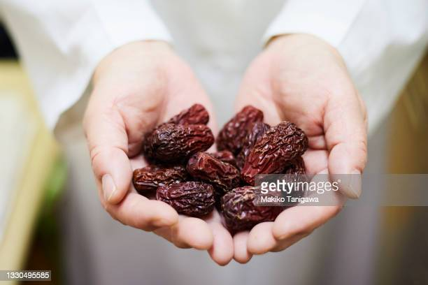 dried jujube in both hands - saitama prefecture stock pictures, royalty-free photos & images