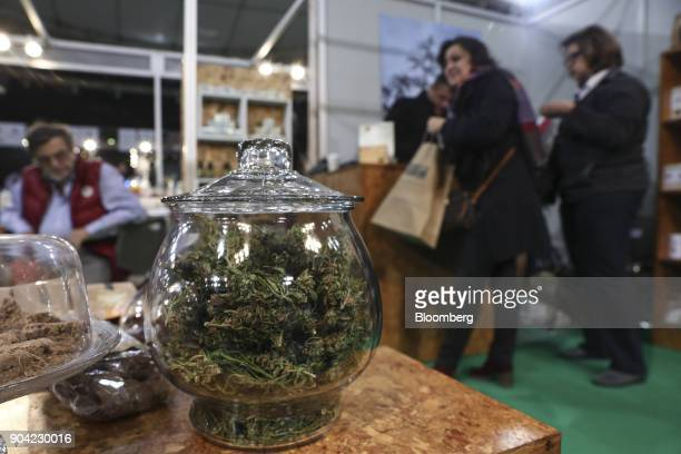 Dried marijuana herbs sit in a glass display jar on an exhibitor's stand at the 1st International Cannabis Expo at the Faliro Sports Pavilion in...