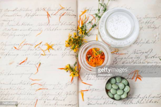 dried medical plants and globuli on old recipe book - homeopathic medicine stock photos and pictures