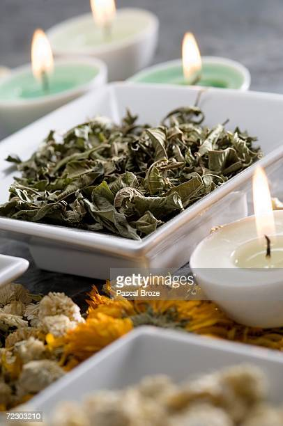 Dried mint and chamomile leaves, candles, close-up