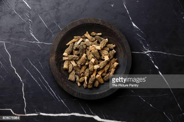Dried morel mushroom on wooden plate on dark marble background