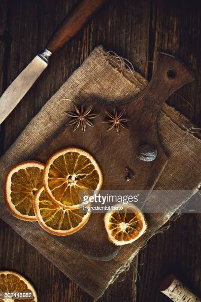 Dried oranges and spices on a wooned board.