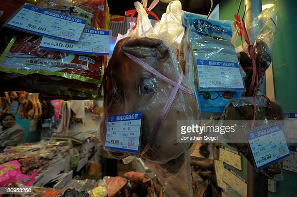 Dried pigs head hangs from the ceiling in the butcher's section of a supermarket in Shanghai, China.