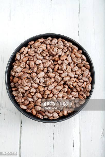dried pinto beans in a bowl - pinto bean stock photos and pictures