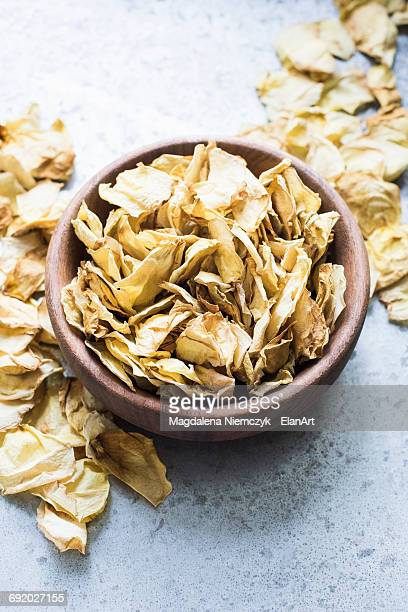 Dried rose petals in a wooden bowl