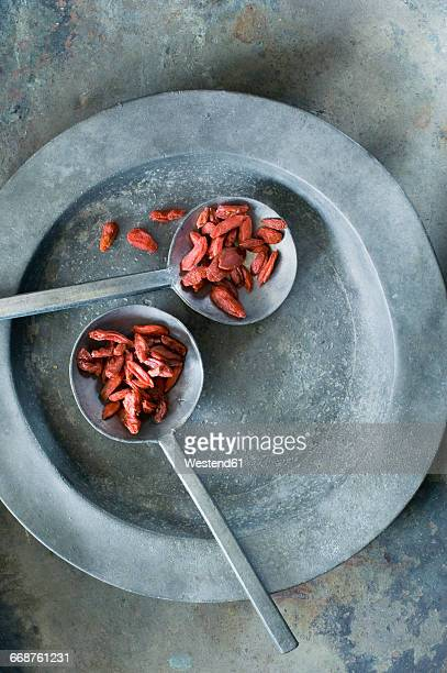 Dried wolfberries on metal spoons and tin plate