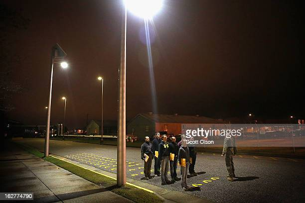 Drill Instructor SSgt Gerald Hemry of Minneapolis Minnesota works with male and female Marine recruits as they arrive for boot camp on February 25...