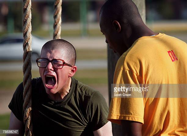 A drill instructor tries to motivate a United States Marine Corps recruit to climb a rope during boot camp March 7 2007 at Parris Island South...