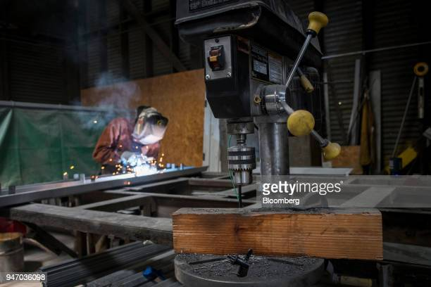 A drill press sits as a worker arc welds at the Metal Manufacturing Co facility in Sacramento California US on Thursday April 12 2018 The Federal...