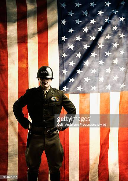 Drill sergeant standing by flag
