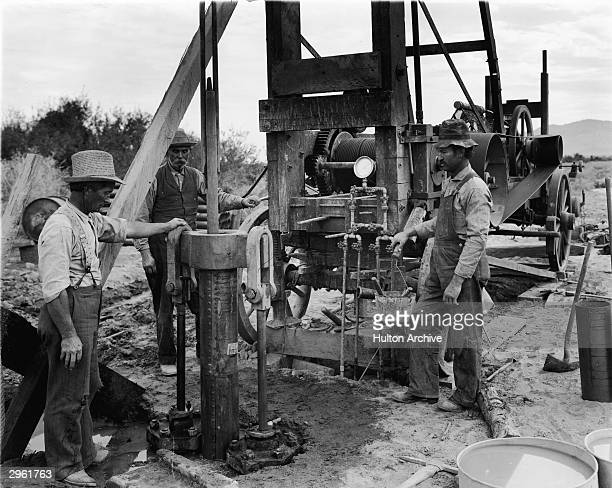 Drill workers operate a hydraulic jack as they create a new water well circa 1911