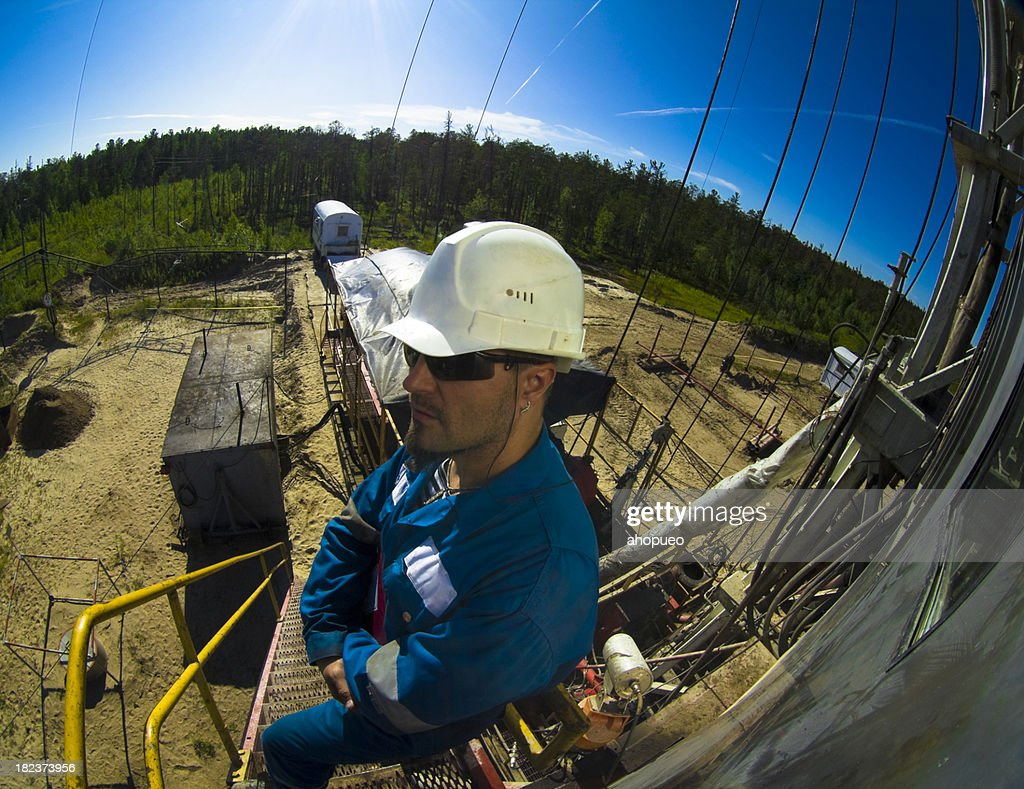 Driller standing on the ladder : Stock Photo