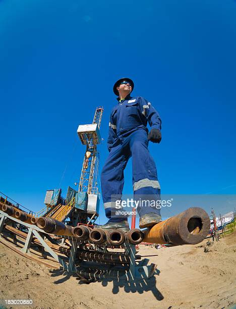 Drilling engineer giant in front of oil rig