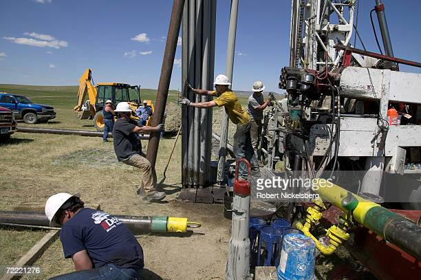 Drilling hands prepare to tighten 10' metal pipe casing that will be connected and fitted into a drilled coal bed methane well for natural gas...