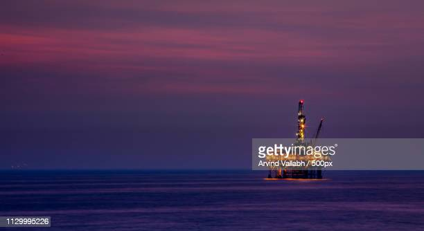 drilling rig at purple dusk - oil rig stock pictures, royalty-free photos & images