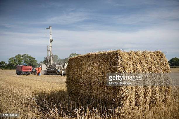 drilling rig in field with hay bale in foreground - モーペス ストックフォトと画像