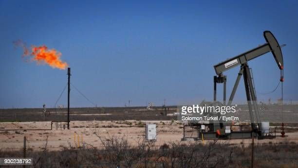 drilling rig on field against clear blue sky - solomon turkel stock pictures, royalty-free photos & images