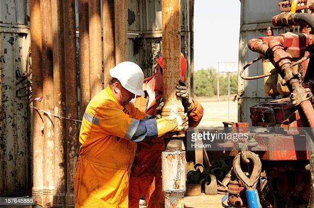 Drilling rig workers in orange uniform