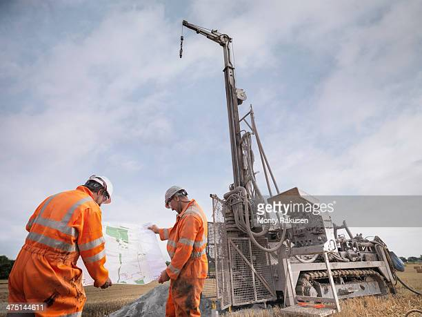 Drilling rig workers inspecting map in field