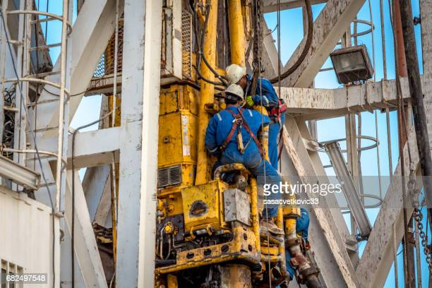 drilling rig workers - safety harness stock pictures, royalty-free photos & images